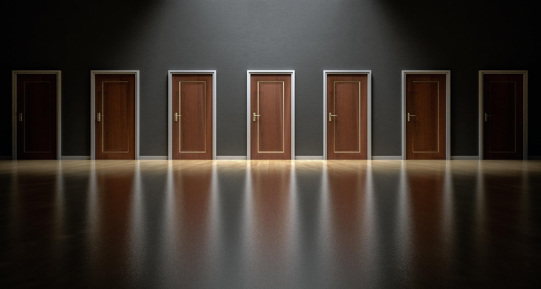 Dark room with endless row of wooden doors