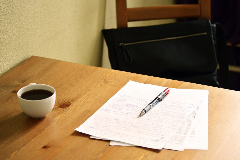 photo of a wooden desk with coffee cup, paper and pen